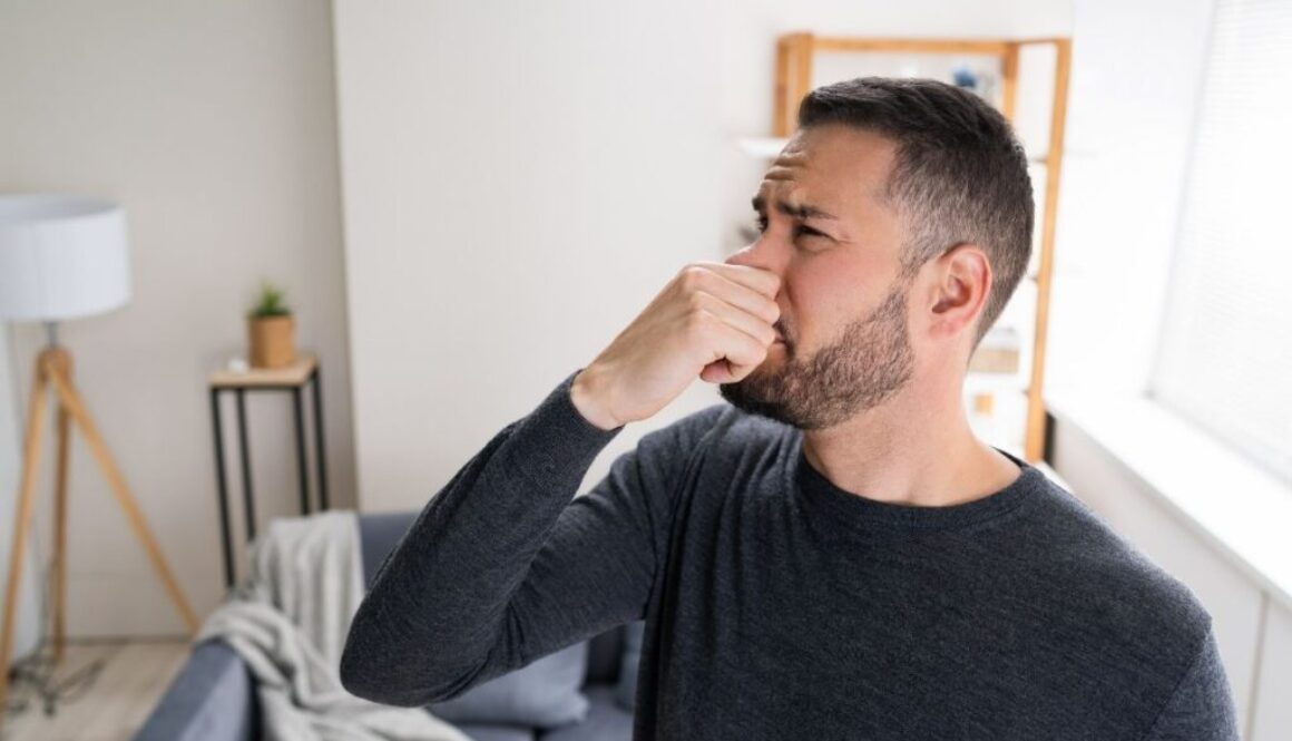 Man covering his nose to not smell his balls